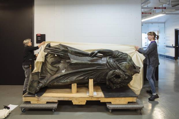 Museum technicians Helene Giguere, left, and Roxanne Bellemare, right, remove a protective tarp from the body of the Queen Victoria statue at the Musee de la Civilization archives in Quebec City on Monday, May 15, 2017.