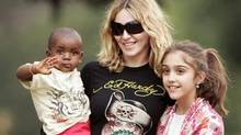 Madonna (pictured with her son, David, and daughter, Lourdes) wears an Ed Hardy tee in Malawi earlier this year.