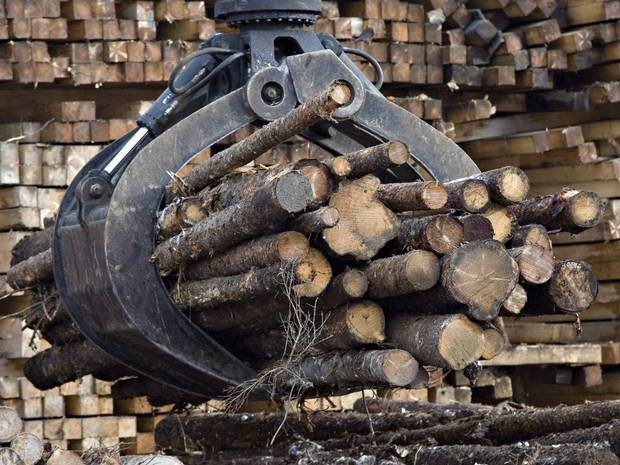 Workers pile logs at a softwood lumber sawmill in Saguenay, Que., on Nov. 14, 2008. The federal government needs to offer money, training and incentives to ensure a technological revolution in the forestry industry creates well-paid jobs at home rather than abroad.