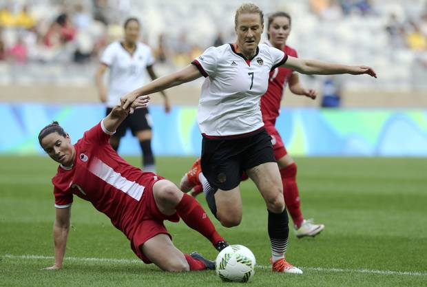 Rhian Wilkinson (CAN) of Canada falls as she fights for the ball with Melanie Behringer (GER) of Germany.