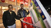 "Cleveland Jones, 22, and Devonte Hubbard, 20, leave Target after the television sale at 4 o'clock in the morning in Tonawanda, New York during ""Black Friday,"" on November 23, 2012. (JENNIFER ROBERTS FOR THE GLOBE AND MAIL)"