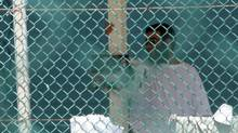 Omar Khadr is seen through the fence at the U.S. detention centre in Guantanamo Bay's on Oct. 23, 2010. (Colin Perkel/Colin Perkel/The Canadian Press)