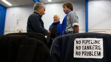 Anti-pipeline stickers line the back of a jacket as Douglas Channel Watch members Dave Shannon, Dieter Wagner and Murray Minchin prepare to address publich hearings into the Enbridge Northern Gateway Project in Kitamaat Village, B.C., on Wednesday. (Darryl Dyck/The Canadian Press)