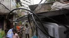 Indian people walk a narrow lane as high-voltage cables come out from an power meter at a slum in Mumbai, India, Friday, Aug. 3, 2012. (Rajanish Kakade/AP)