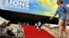 A woman walks past the Cannes Festival Palace where takes place the Cannes Lions 2010 International Advertising Festival in Cannes, June 23, 2010. (Sebastien Nogier/Reuters)