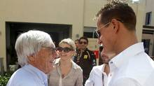 Bernie Ecclestone, president and CEO of Formula One Management, left, shakes hands with Mercedes driver Michael Schumacher of Germany in the paddock ahead the Emirates Formula One Grand Prix at the Yas Marina racetrack in Abu Dhabi, United Arab Emirates, Sunday, Nov. 13, 2011. The head of Formula One expressed doubts on Saturday whether the 2012 United States Grand Prix in Austin, Texas, will go ahead as scheduled. (Luca Bruno/AP Photo/Luca Bruno)