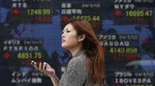 A pedestrian holding her mobile phone walks past an electronic board showing the stock market indices of various countries outside a brokerage in Tokyo May 13, 2014. (YUYA SHINO/REUTERS)