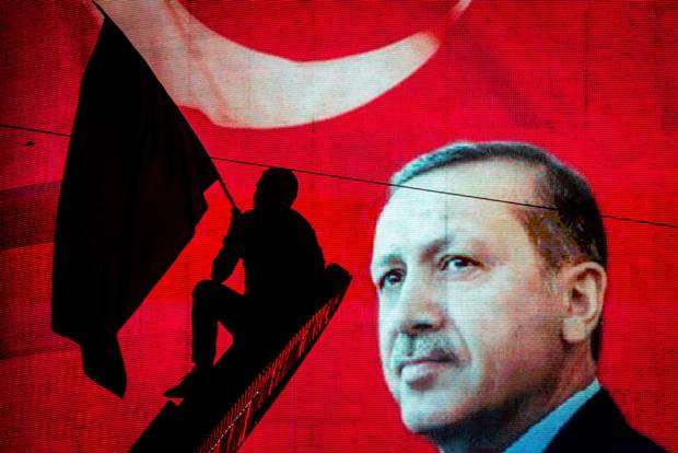 A supporter of Turkish President Recep Tayyip Erdogan waves a flag against an electronic billboard during a rally in Kizilay Square on July 18 in Ankara, Turkey. Continuing raids across the country have seen thousands detained, suspended or arrested, including high ranking soldiers, judges and police officers.