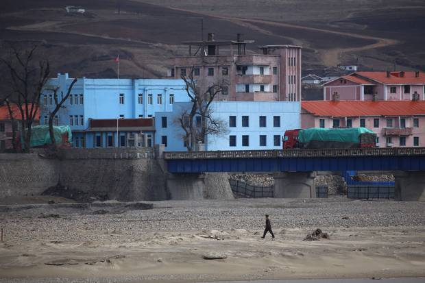 A uniformed North Korean man walks along the North Korean side of the Tumen River, which separates the isolated regime from China. Despite recent tensions, trucks are still crossing the border.