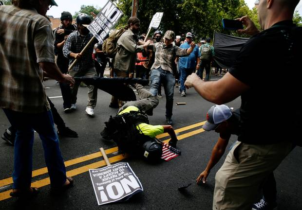 A man hits the pavement during a clash between members of white nationalist protesters against a group of counter-protesters in Charlottesville.