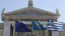 Flags from right, Greek, National Bank of Greece and the European Union flags wave outside the headquarters of the National Bank of Greece. (Petros Giannakouris/AP)