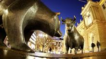 The bull and bear bronze statue stands outside the stock market, Deutsche Boerse AG, in Frankfurt, Germany. (Michael Probst/AP)