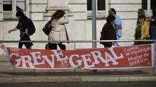 People walk by a banner in downtown Lisbon calling for a general strike on Nov. 24 in protest against government austerity measures. (Armando Franca)