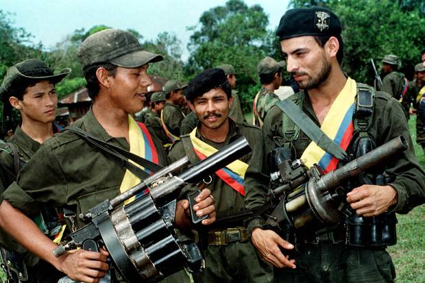 FARC fighters pose with their weapons after a patrol in the jungle near the town of Miraflores on Aug. 7, 1998.