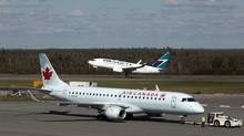 A Westjet aircraft takes off as an Air Canada jet is towed on the tarmac at the Halifax airport on Tuesday, Sept. 20, 2011. (Andrew Vaughan/THE CANADIAN PRESS)