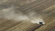 Dust is blown behind a combine harvesting corn during last summer's drought near Coy, Ark. (Danny Johnston/AP)