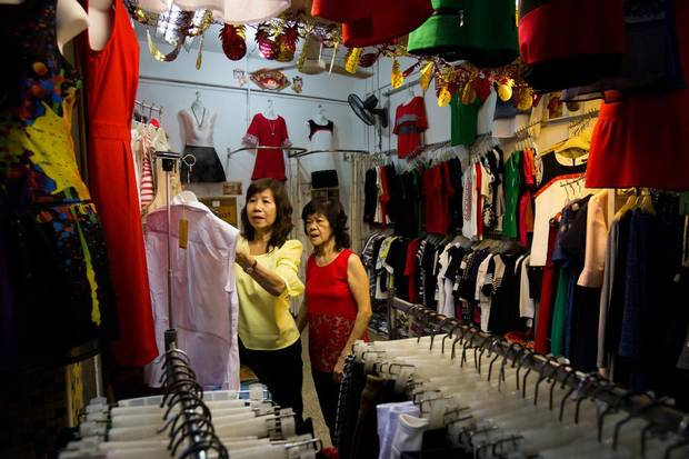 A vendor looks at clothing in a store at the Teck Ghee Court Market & Food Centre in the Ang Mo Kio area of Singapore, on Saturday, Feb. 20, 2016.