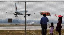 People watch airplanes land as they stand outside Toronto Pearson Airport in Mississauga on July 15, 2012. (For The Globe and Mail)