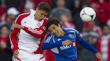 Toronto FC's Adrian Cann (left) and Montreal Impact's Bernardo Corradi battle for the ball during the first half of game 3 Canadian Championship action in Toronto on Saturday May 9, 2012. (Frank Gunn/THE CANADIAN PRESS/Frank Gunn/THE CANADIAN PRESS)