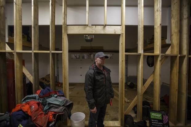 Kirby Byrne stands next to a support wall in the garage, intended to mitigate structural damage, after the family was forced to move out of their Fort McMurray house.