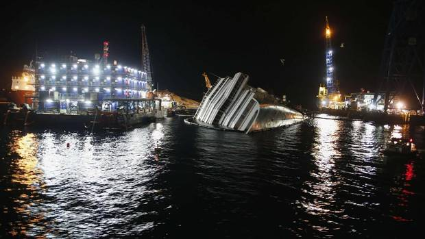 The capsized cruise liner Costa Concordia is surrounded by cranes during ongoing salvage operations in Giglio harbour Jan. 10, 2013. This Sunday marks the one-year anniversary of the shipwreck in which 32 people died. (TONY GENTILE/REUTERS)
