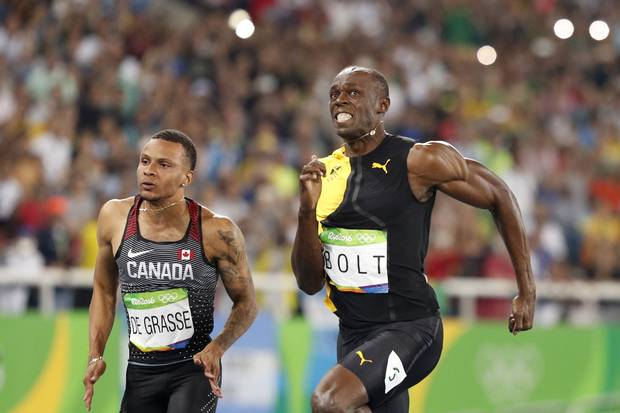 Andre De Grasse and Usain Bolt compete in the Men's 100m Final during the athletics event at the Rio 2016 Olympic Games at the Olympic Stadium in Rio de Janeiro on August 14, 2016.