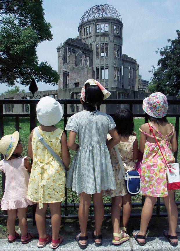 Japanese children look up at the Atomic Bomb Dome in Hiroshima Peace Memorial Park, Japan, August 5, 2000, on the eve of the 55th anniversary of the world's first atomic bombing. More than 140,000 people were killed and many more injured after the United States dropped an atomic bomb on the Japanese city of Hiroshima on August 6, 1945. Three days later a second atom bomb was dropped on Nagasaki.
