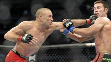 Georges St-Pierre, left, battles against Jake Shields during the welter weight championship match at UFC 129 in Toronto on April 30, 2011. (Nathan Denette/The Canadian Press)