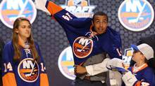 Joshua Ho-Sang puts on a team sweater after being selected as the number twenty-eight overall pick to the New York Islanders in the first round of the 2014 NHL Draft at Wells Fargo Center. (Bill Streicher/USA Today Sports)