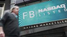 A man walks past a sign welcoming Facebook to the NASDAQ Marketsite in New York May 18, 2012. (BRENDAN MCDERMID/REUTERS)