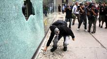 G20 summit protesters smash the window of a business front on Queen Street West near Bay Street in downtown Toronto. (Chris Young/Chris Young/The Canadian Press)