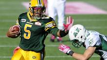 Edmonton Eskimos' quarterback Kerry Joseph (L) runs against Saskatchewan Roughriders' Craig Butler during their CFL game in Edmonton October 13, 2012. (DAN RIEDLHUBER/REUTERS)