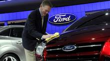 Ford CEO Alan Mulally shines the hood of a Ford Focus. (HO)