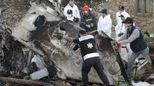 A forensic team recovers human remains among the wreckage of crashed TransAsia Airways flight GE222 on the outlying island of Penghu, Taiwan, Thursday, July 24, 2014. Stormy weather on the trailing edge of Typhoon Matmo was the likely cause of the plane crash that killed more than 40 people, the airline said Thursday. (Wally Santana/AP)