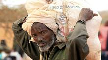A Somali refugee carries leaves the World Food Program distribution centre at the Ifo refugee camp in Dadaab, near the Kenya-Somalia border, on Aug. 1, 2011. (Thomas Mukoya/Reuters)