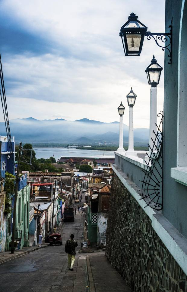 The majestic Sierra Maestra mountains rise in contrast against the humble streets of Santiago de Cuba.