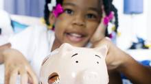 girl piggybank money saving spending (© 2010 Photos.com, a division of Getty Images. All rights reserved.)