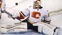 Calgary Flames goalie Leland Irving keeps his eyes on the puck as he drops back to make a save against the Boston Bruins during the first period of an NHL game in Boston, Thursday Jan. 5, 2012. (Charles Krupa/AP)