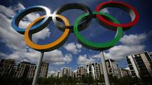 A set of Olympic rings are seen standing in front of apartments for athletes (Matt Dunham/AP)