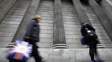 A woman carries a shopping bag decorated with a Union flag past the columns of the Bank of England in the City of London, July 3, 2012. (ANDREW WINNING/REUTERS)