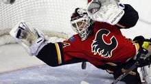 Calgary Flames goalie Miikka Kiprusoff, from Finland, dives on the puck during second period NHL action against the Columbus Blue Jackets in Calgary, Alta., on Friday, March 29, 2013. (Jeff McIntosh/THE CANADIAN PRESS)