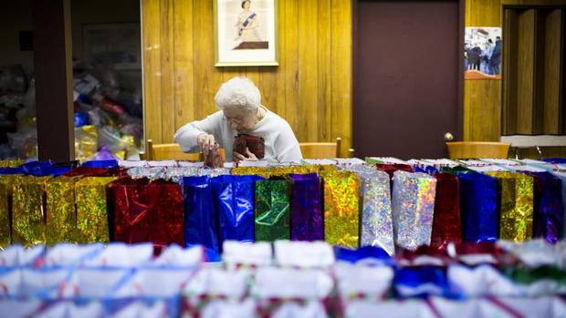 Hellen Tataren, a volunteer with the Mission to Seafarers in Vancouver, wraps socks as Christmas gifts for sailors on December 14, 2012. (John Lehmann/The Globe and Mail)
