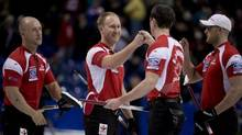 Canada skip Brad Jacobs, centre, celebrates his teams win over Denmark with E.J. Harnden, centre right, and Ryan Harnden, right, as Ryan Fry looks on following a page 3-4 playoff draw at the World Men's Curling Championship in Victoria, B.C., on Saturday, April 6, 2013. (JONATHAN HAYWARD/THE CANADIAN PRESS)