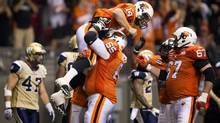 B.C. Lions' Ben Archibald, 65, lifts quarterback Travis Lulay, 14, after Lulay scored a touchdown as teammate Jon Hameister-Ries, 67, joins in the celebration while Winnipeg Blue Bombers' Pierre-Luc Labbe, left, walks away during the second half of a CFL game in Vancouver, B.C., on Friday June 29, 2012. (DARRYL DYCK/THE CANADIAN PRESS)