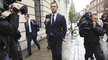 Andy Coulson, middle, former editor of the News of the World and former spokesman for Britian's Prime Minister David Cameron, leaves after giving evidence before the Leveson Inquiry into the ethics and practices of the media at the High Court in central London on Thursday. (OliviaHarris/Reuters/OliviaHarris/Reuters)