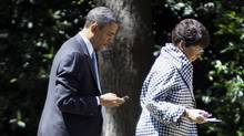 U.S. President Barack Obama checks his BlackBerry while walking with senior adviser Valerie Jarrett towards the Oval Office at the White House in Washington, May 4, 2010. (Larry Downing/REUTERS/Larry Downing/REUTERS)