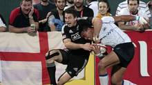 New Zealand's Kurt Baker, left, fights for the ball against Samoa's Lio Lolo during their Sevens World Series Cup final rugby match at The Sevens stadium in Dubai December 1, 2012. (AHMED JADALLAH/REUTERS)