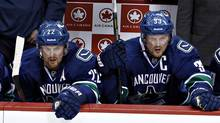 Vancouver Canucks Henrik Sedin and his brother Daniel, left, watch game play against the San Jose Sharks during Game 1 of their NHL Western Conference quarter-final hockey playoff in Vancouver, May 1, 2013. (ANDY CLARK/REUTERS)