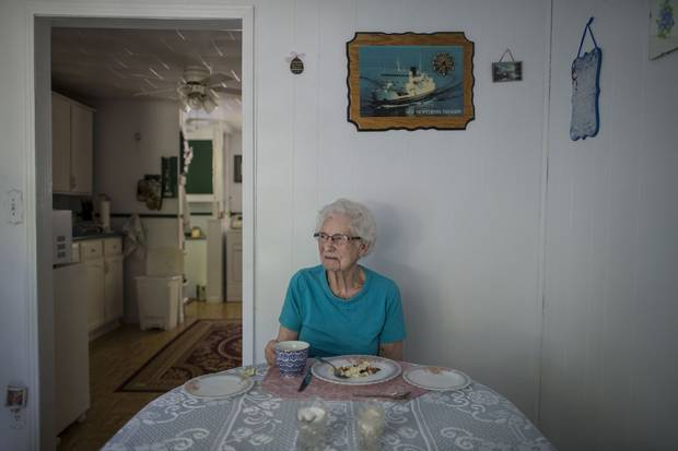 Cressie Roberts sits at her table with a plate of fish and brewis and a cup of tea for a midday meal. 'I'm not happy about leaving. I'd love to live here forever but I know I can't,' says of Little Bay Islands.