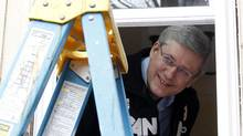 Canada's Prime Minister Stephen Harper sticks his head out of a window he helped install during a campaign stop in Ottawa April 11, 2011. (BLAIR GABLE/Blair Gable/ Reuters)